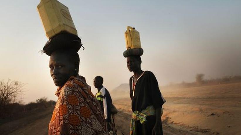 Umwelt: Frauen im Sudan transportieren Wasser in Kanistern auf ihren Köpfen.