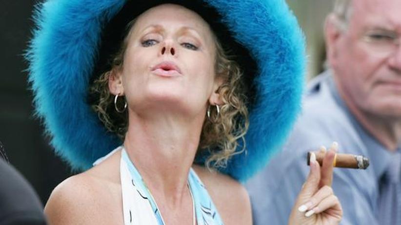 Rauchverbot: Eine Besucherin eines Pferderennens in Auckland, Neuseeland, raucht eine Zigarre.