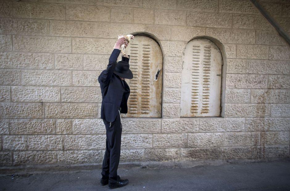 Dieser Ultra-Orthodoxe in Mea Shearim schwenkt das Huhn selbst über den eigenen Kopf.