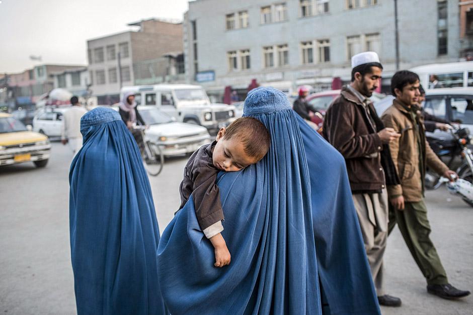 Mittagschläfchen auf Mamas Schulter. Die meisten Frauen in Kabul tragen eine Burka.