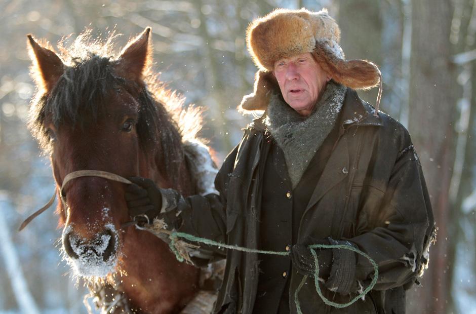 Yuri und sein Pferd transportieren Heu zu seiner kleinen Farm in der Nähe des Dorfes Yukhovichi.
