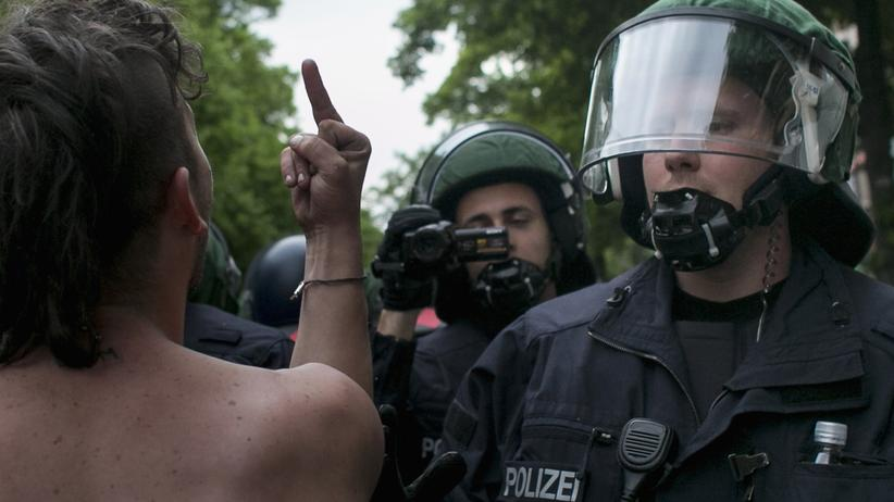 Polizeigewalt: 1. Mai in Berlin: Ein Demonstrant zeigt einem Polizisten den Mittelfinger.