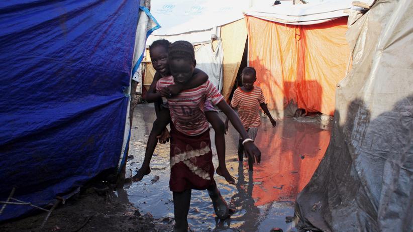 Südsudan: Ein südsudanesisches Flüchtlingsmädchen trägt in einem überfluteten Camp in Malakal einen Jungen auf dem Rücken.