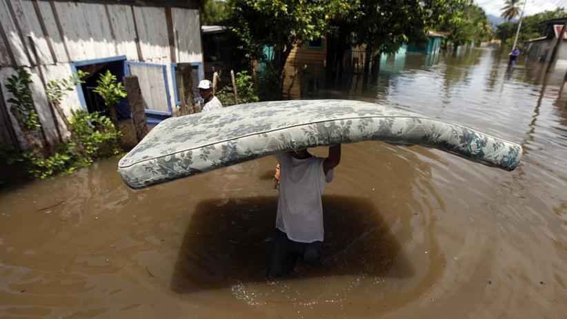 Germanwatch: Ein Jugendlicher trägt eine Matratze durch die überschwemmte argentinische Region Potrerillos. (Archiv)
