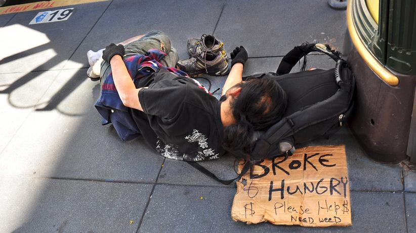 San Francisco: SAN FRANCISCO, CA - OCTOBER 4, 2013: A homeless man sleeps on a sidewalk in San Francisco's Union Square district. His sign declares that he is 'broke and hungry' and 'needs weed.'