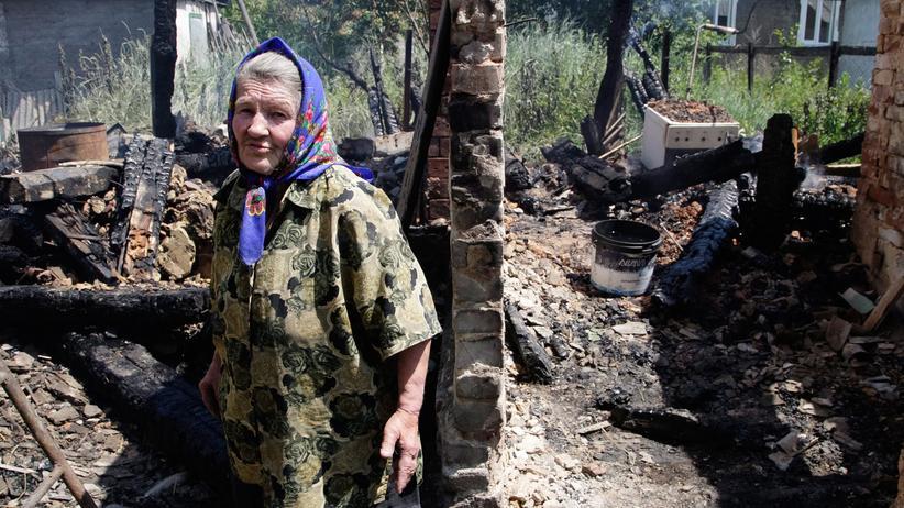 Eine Frau, die in einem Außenbezirk von Donezk die Zerstörung des Krieges ansieht.