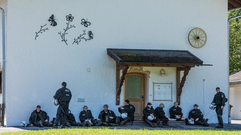 Zehn der 20.000 Polizisten ruhen sich in Garmisch-Partenkirchen im Schatten aus.