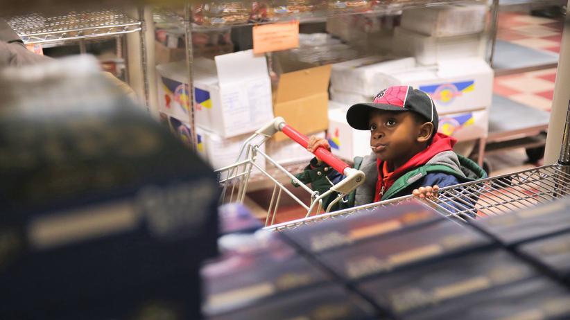Soziale Ungleichheit: Ein kleiner Junge in einer Lebensmittelkammer in New York. Arme können hier kostenlos Nahrung erhalten.