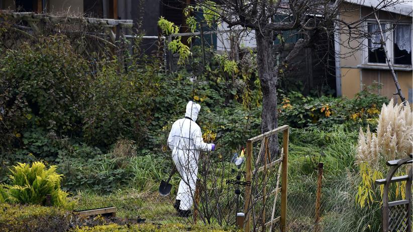 Polizisten untersuchen einen Garten in Luckenwalde/Brandenburg