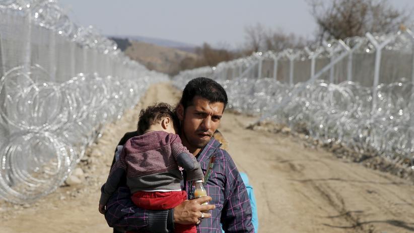 Flüchtlingskrise: Verzweiflung: Ein Flüchtling aus Afghanistan trägt ein Kind an der griechisch-mazedonischen Grenze in Gevgelija
