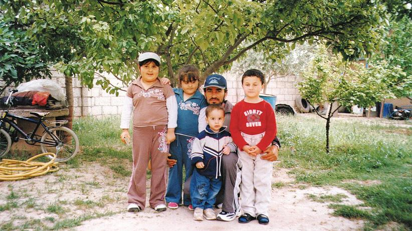 Syria: Tel Goran before the war: A father with his children in the Kefarkis family garden.