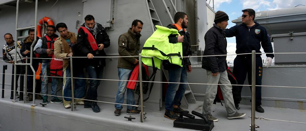Flüchtlinge warten am Samstag an einem Hafen auf Lesbos