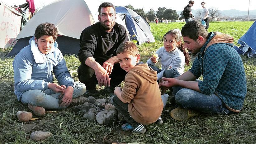 Griechenland: Der syrische Flüchtling Mohamed Aloloh und seine Kinder rösten Kartoffeln an einer Feuerstelle in unmittelbarer Nähe zur mazedonischen Grenze.