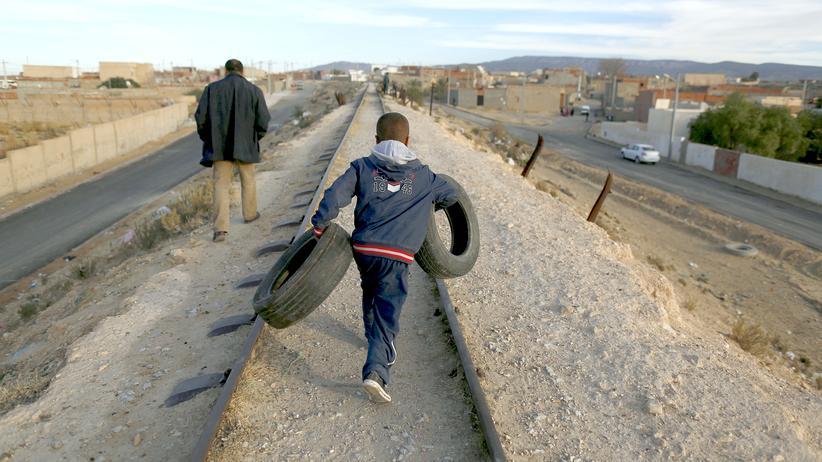 Tunesien: Szene in einem armen Teil der tunesischen Stadt Kasserine: Ein Junge trägt alte Reifen, die er auf einer Müllhalde gesammelt hat.