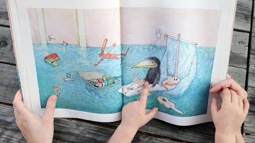 Kitaqualität: Gemeinsam mit einem Kind ein Bilderbuch anschauen: Dafür muss eine Erzieherin im Kitaalltag erst mal die Ruhe finden.