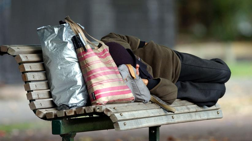 Obdachloser Mensch schläft auf einer Bank