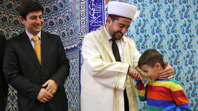 Ditib: Ein Imam in einer Ditib-Moschee in Frankfurt/Main bei einem Fest mit einem Jungen und dessen Vater
