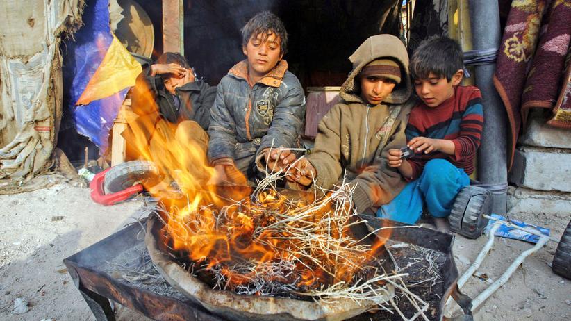 Unicef: Kinder sitzen am Feuer in der irakischen Stadt Nadschaf.