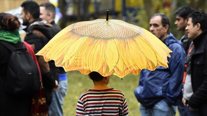 Migration: Ein minderjähriger Geflüchteter ist mit Regenschirm in einer temporären Unterkunft in Berlin-Tegel unterwegs.