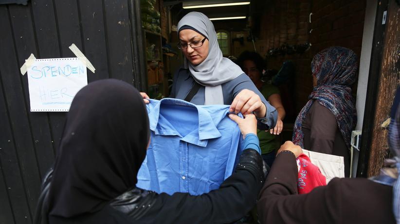 Bertelsmann-Stiftung: Eine Flüchtlingshelferin verteilt Kleider an Asylbewerber in Berlin
