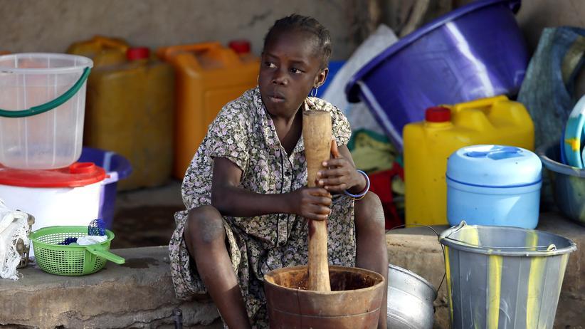 Hunger: Ein von Boko Haram aus ihrem Heimatort vertriebenes Mädchen mahlt in einem Notaufnahmelager Getreide.