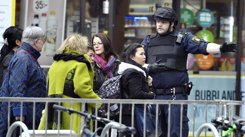LKW-Attacke: Ein Polizist in Stockholm leitet Passanten an kurz nach dem Anschlag in der Stadt.