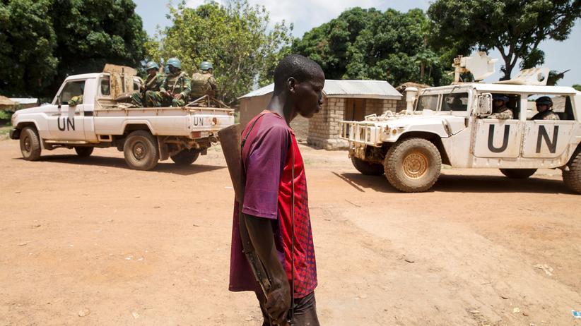 Zentralafrikanische Republik: Ein Milizionär und (im Hintergrund) Soldaten der UN-Friedensmission in einem Dorf in der Zentralafrikanischen Republik