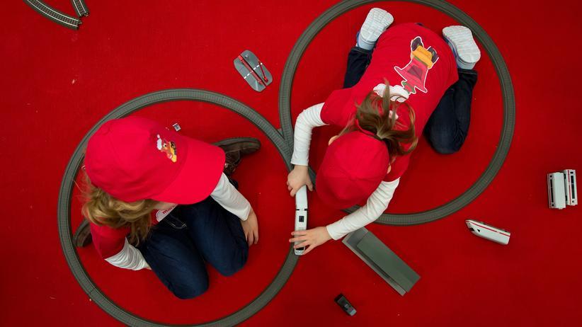 Unicef: Zwei Mädchen spielen mit Spielzeugzügen.