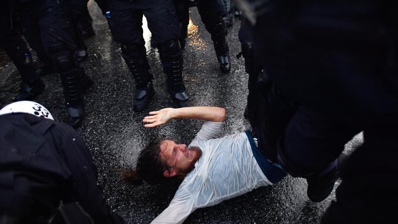 Polizei Hamburg: Berechtigter Einsatz? Ein Demonstrant wird von Polizistin in Hamburg überwältigt.