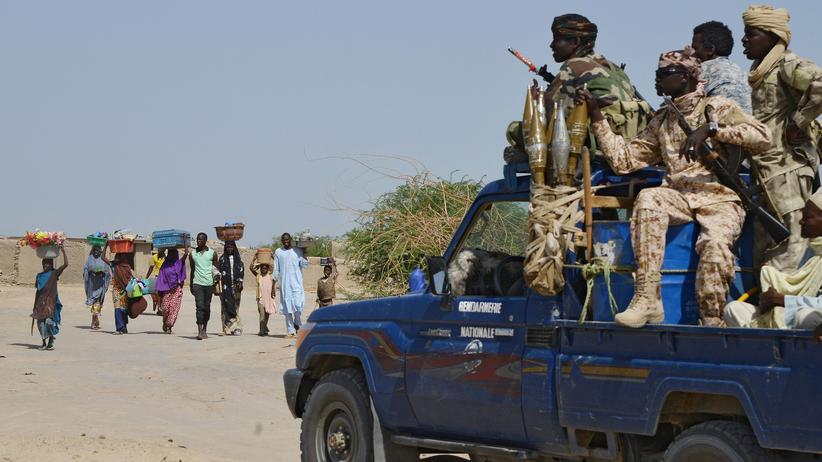 Amnesty International: Eine Gruppe von Frauen und Kindern passiert im Tschad auf der Flucht vor der islamistischen Terrororganisation Boko Haram einen Posten von Sicherheitskräften.