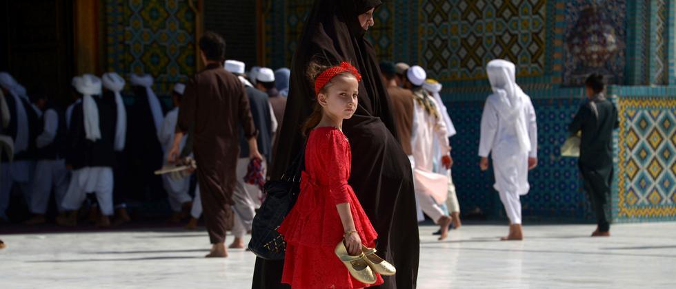 Ein afghanisches Mädchen läuft mit ihrer Mutter durch den Hof der Blauen Moschee in Masar e-Scharif