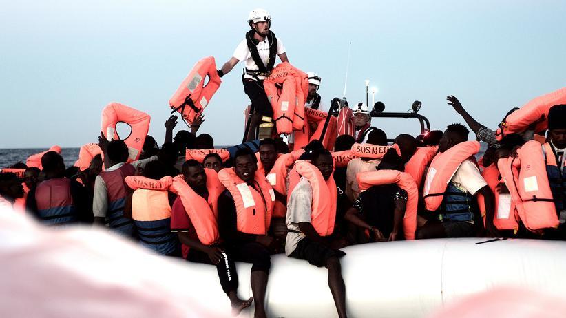 """Flüchtlingsschiff """"Aquarius"""": Erste Maßnahme nach dem Auffinden: Besatzungsmitglieder des Seenotrettungsschiffes Aquarius versorgen Flüchtlinge auf einem Schlauchboot mit Schwimmwesten."""