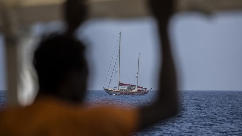 """Proactiva Open Arms: Ein geretteter Migrant auf dem Rettungsschiff """"Open Arms"""" blickt auf das Segelboot """"Astral"""" der Hilfsorganisation Proactiva Open Arms."""