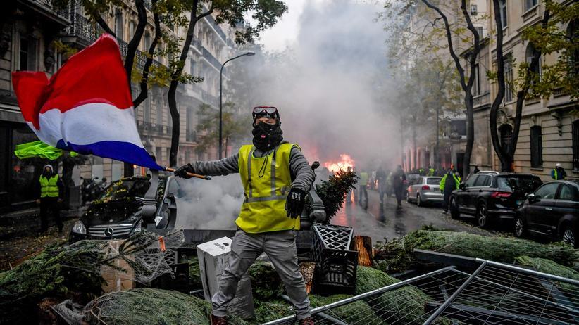 Gelbwesten: Ausschreitungen im Advent, brennende Barrikaden in Paris: ein Anhänger der Gelbwesten inmitten der eskalierenden Proteste