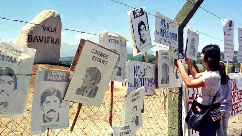 Chile: Am Zaun um das Gelände der Colonia Dignidad hängen Fotos von Vermissten.