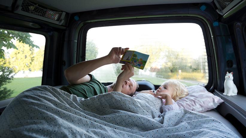 Vorlesestudie 2019: Ein Vater schaut mit seinem Kind in den Ferien ein Buch an. Väter lesen jedoch deutlich seltener vor als Mütter.