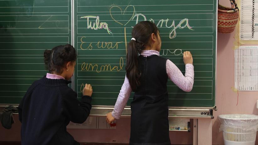 Gökay Sofuoğlu: Grundschülerinnen in Berlin üben das Schreiben an der Tafel. Die Lerninhalte regelt das jeweilige Bundesland – bei privaten wie öffentlichen Schulen.