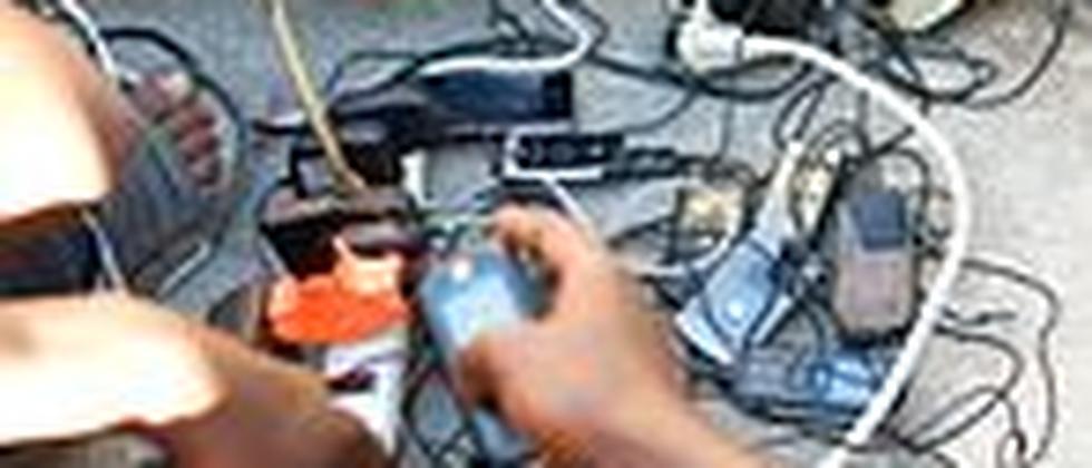 Vor dem zerstörten Gebäude von Radio Caraibes in Port-au-Prince laden Haitianer ihre Handys auf. Die Radiostation liefert mit einem Generator den Strom dafür.
