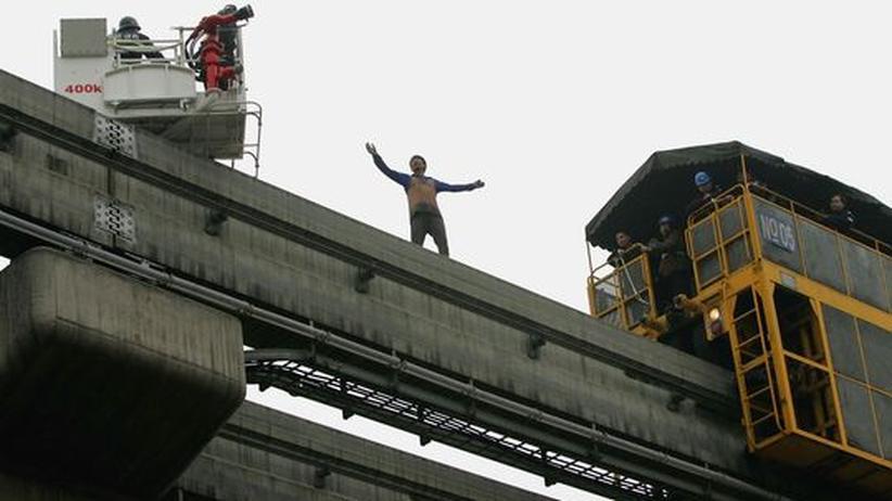 Irrwitz der Woche: In Chongqing in China versuchen Rettungskräfte einen Mann daran zu hindern, sich zu töten
