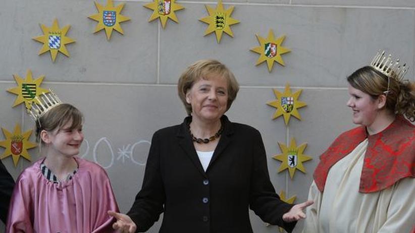 Angela Merkel posiert mit kostuemierten jungen Sternsingerinnen im Bundeskanzleramt