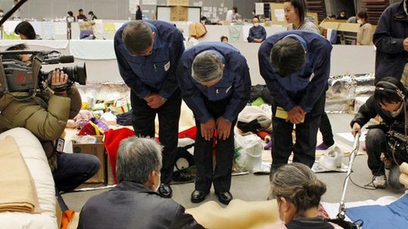 Tepco-Vizepräsident Norio Tsuzumi (Mitte) bittet in einem Notquartier die Bewohner der Region am Kraftwerk Fukushima um Verzeihung