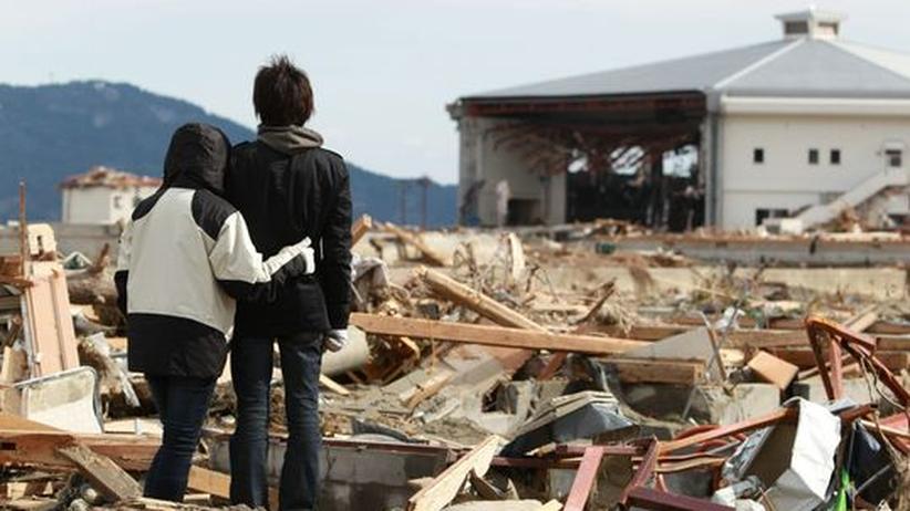 Zwei Geschwister blicken auf die Überreste ihres Hauses in der japanischen Stadt Rikuzentakata.