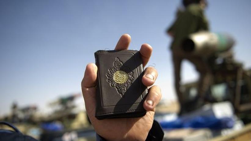 Religionen und Gewalt: Libysche Rebellen halten einen Koran in die Kamera. Im Hintergrund sind bewaffnete Fahrzeuge zu erkennen.