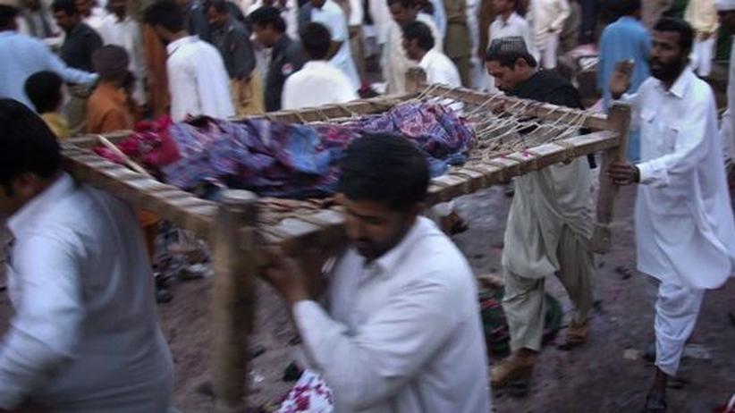 Terrorismus: Hilfskräfte tragen ein Opfer des Selbstmordattentats in Dera Ghazi Khan
