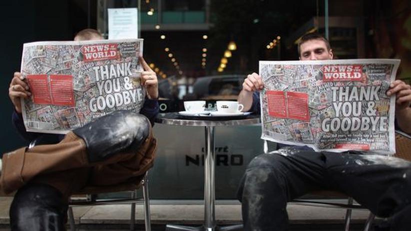 """Boulevardpresse: Zwei Bauarbeiter in Manchester lesen die letzte Ausgabe der """"News of the World"""""""