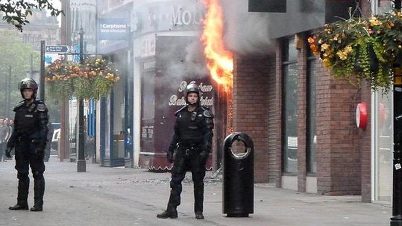 Krawalle in Großbritannien: Polizisten stehen vor einem brennenden Geschäft in der Innenstadt von Manchester.