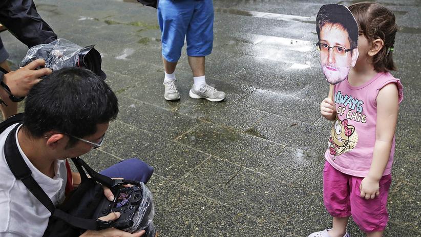 Ex-Geheimdienstler: Ein kleines Mädchen in Hongkong hält sich eine Maske mit dem Gesicht von Edward Snowden vor ihr Gesicht.