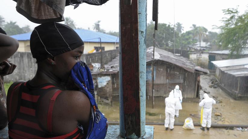 Ebola in Westafrika: Helfer in Schutzanzügen (Hintergrund) in Monrovia, Liberia