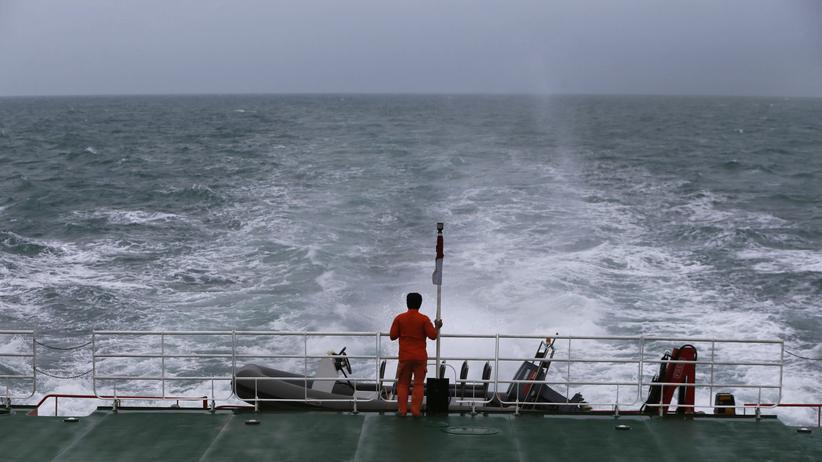 Ein Helfer steht an Deck eines Rettungsschiffes, auf der Suche nach Passagieren des vermissten AirAsia-Flugzeugs