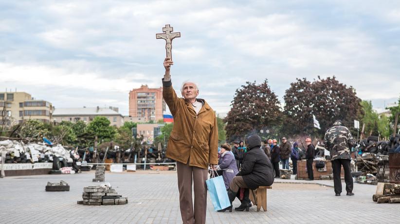 Ein orthodoxer Christ steht vor einem Gebäude im ukrainischen Donezk, das als Zentrale der prorussischen Separatisten dient.
